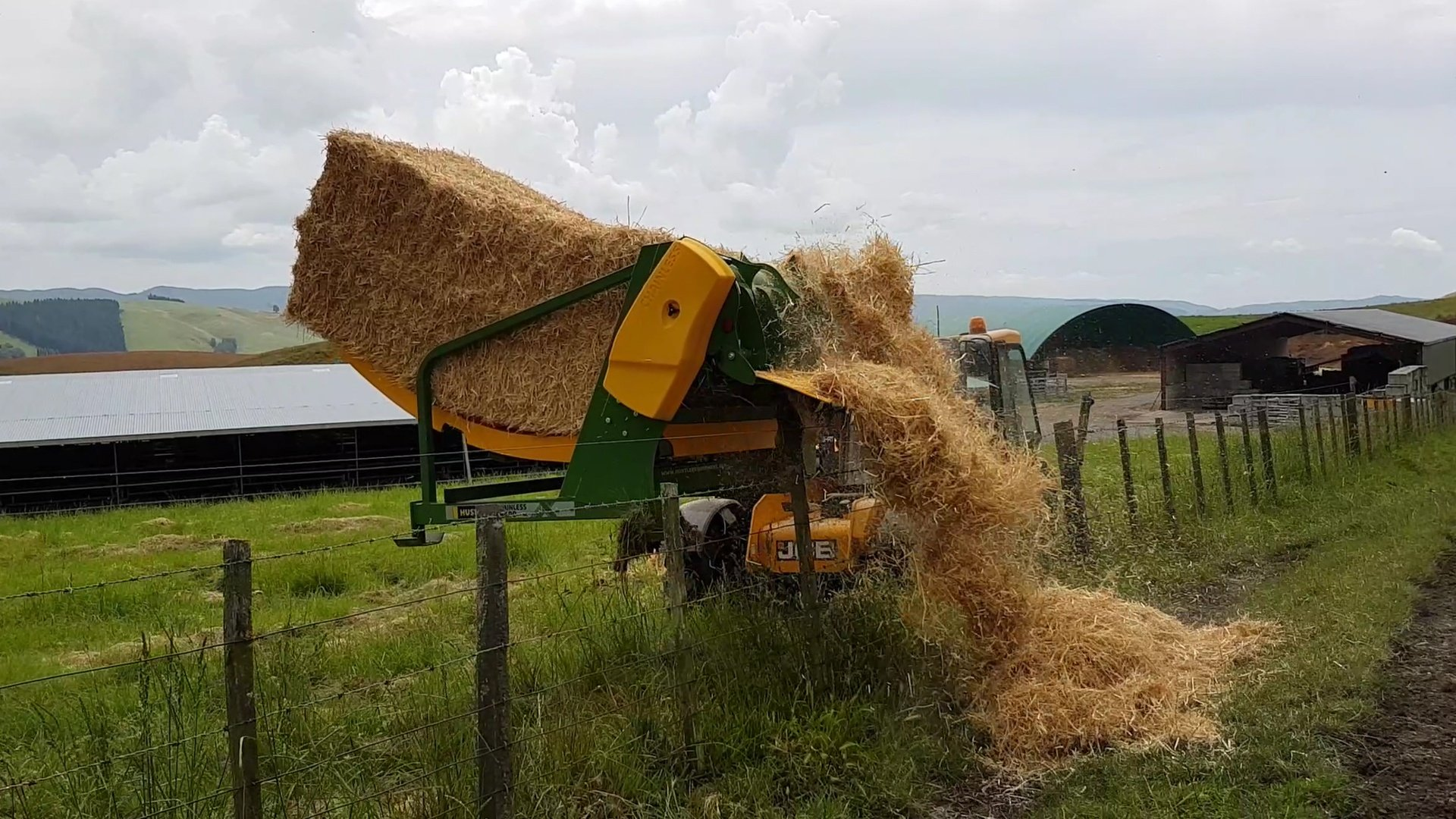 Feeding square bales over a fence.jpg